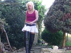 Naughty blonde AxaJay lets you upskirt at her pussy while smoking outdoors in sexy leather boots